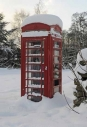 Old-style red telephone box under snow